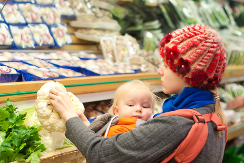 Young mother with toddler girl shopping in supermarket