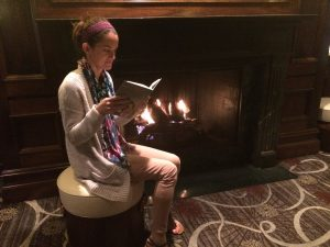 Reading by the fire at the hotel.